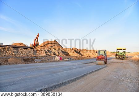 Paving Roller Machine During Road Work. Road Roller At Construction Site For Paving Works. Screeding