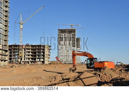 Excavator Working On Road Construction. Backhoe On Earthworks. Heavy Construction Equipment Machines