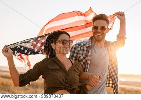 Nice happy couple holding hands together while strolling with american flag on nature at summer