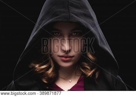 Close-up Portrait Of A Secretive Young Girl In A Deep Dark Hood On A Black Background. The Concept O