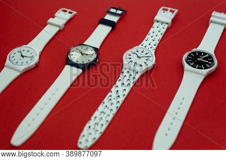 London, Gb 07.10.2020 - Four Swatch Childrens Swiss Made Quartz Watch Isolated On Red Background. Bl