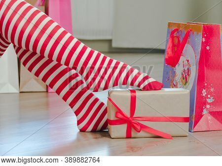 Womens Legs In Striped Stockings And New Years Gifts. Santa Woman Legs In Striped Stockings And Chri