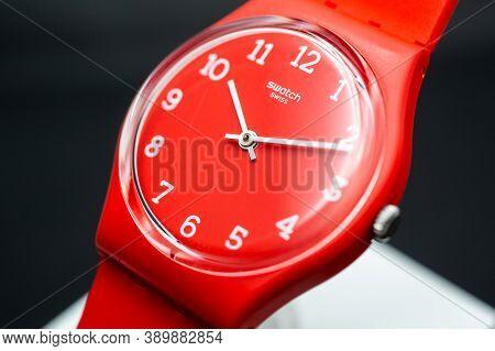 London, Gb 07.10.2020 - Swatch Swiss Made Quartz Watch On Brand Showcase Stand. Red Plastic Case, Bl