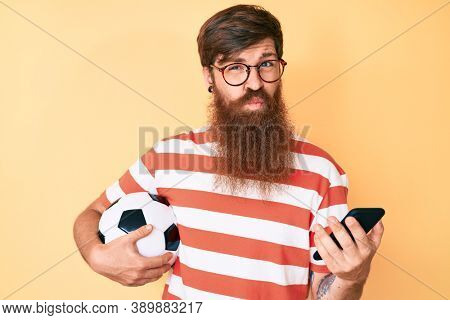Handsome young red head man with long beard holding football ball looking at smartphone looking at the camera blowing a kiss being lovely and sexy. love expression.