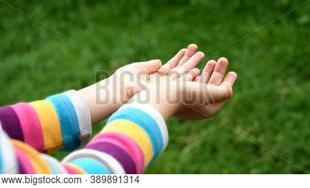 Closeup Of Wet Hands Of Baby Girl In Colorful Striped Sleeve Shirt. Toddler Plays In Drizzle Catchin