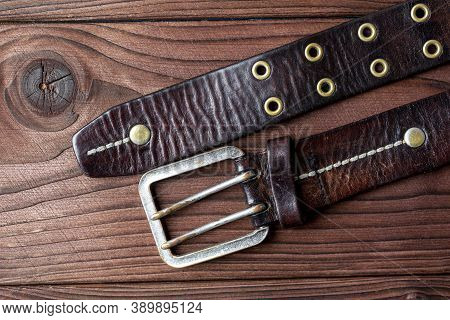 Old Leather Belt With A Buckle On Old Wooden Board. Mens Brown Belt Made Of Genuine Leather With A M