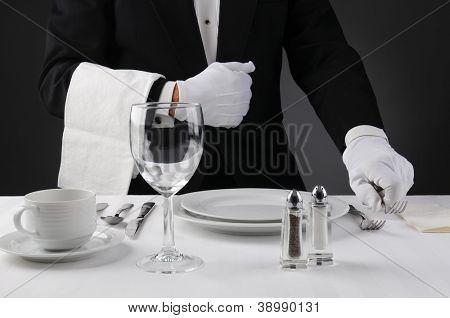 Primer plano de un camarero en un esmoquin poner una mesa de cena formal. Profundidad de campo en horizontal