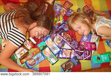 Happy Children Lie In A Heap Of Sweets And Chocolates. Sisters Love Sweets. Little Girls Enjoy Lots