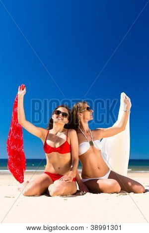 Two Girls enjoying freedom on the beach sitting with cloth in wind and sun at the sea