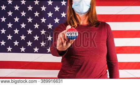 Voting Woman Putting On Vote Button With Face Mask At Elections And American Flag.