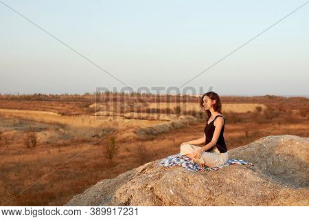 Woman Meditating Yoga Alone At Sunrise Mountains. View From Side. Harmony With Nature. Autumn Landsc