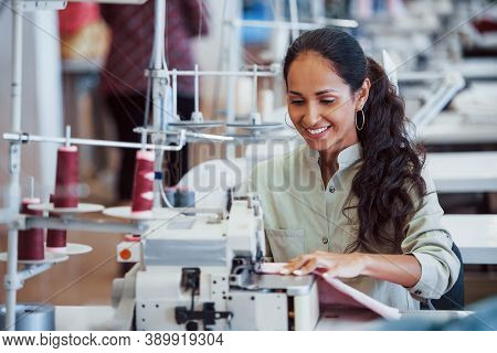 Dressmaker Woman Sews Clothes On Sewing Machine In Factory.