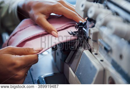 Detailed View Of Dressmaker Woman Sews Clothes On Sewing Machine In Factory.
