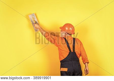 Plaster Trowel Spatula On Yellow Drywall Plasterboard. Plasterer In Working Uniform Plastering Wall