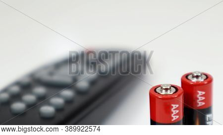Black Tv Remote Control With Aaa Alkaline Batteries In Red And White On A White Background. Battery
