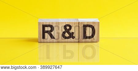 R And D - Research And Development - Word Is Made Of Wooden Building Blocks Lying On The Yellow Tabl
