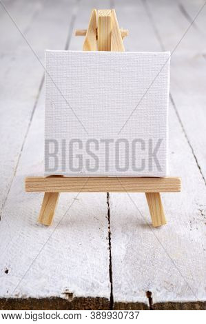 Small Easel With White Blank Cloth On A Wooden Table. Miniature Painting Accessories.