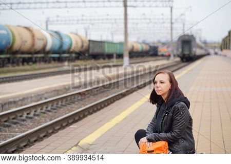 Young Woman Squats On Platform, Waiting For Train. Female Passenger With Backpacks Sitting On Railro