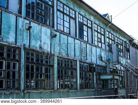 Industrial Weathered Urban Building With Rusting Window Grill And Discoloured Painted Wall Surface