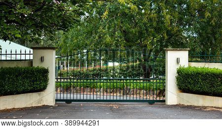 Green Metal Wrought Iron Driveway Property Entrance Gates Set In Concrete  Fence, Garden Shrubs, Tre