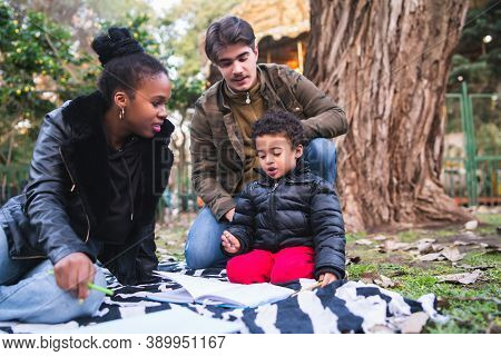 Portrait Of Cute Mixed Race Ethnic Family Having A Good Time Together At The Park Outdoors.