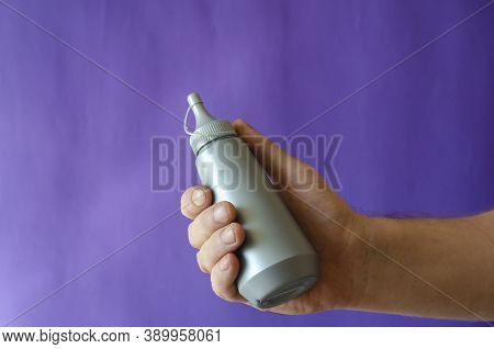 Male Hand And Gray Plastic Bottle Of Syrup. The Man Is Holding A New Bottle Of Sweet Syrup For Ice C