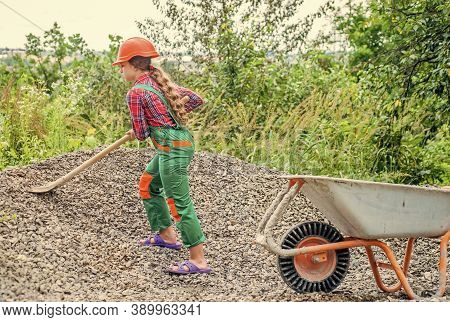 Outdoor Activity. Girl Who Is Transporting Rubble In A Wheelbarrow. Construction Work. Girl Builder