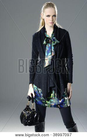 Young fashion model holding handbag posing in light background