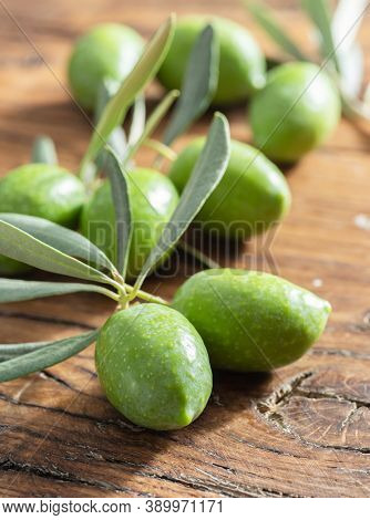 Green natural olives with olive leaves on a vintage old wooden table.