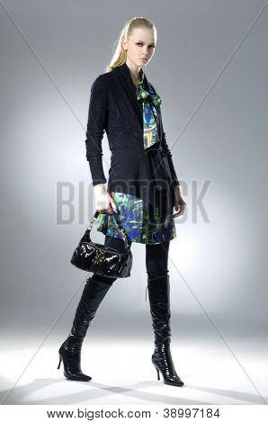 fashion model holding handbag posing walking in studio