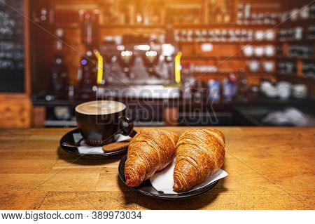 Freshly Baked Croissants And Cup Of Coffee On Wooden Table With Blur Cafeteria As Background