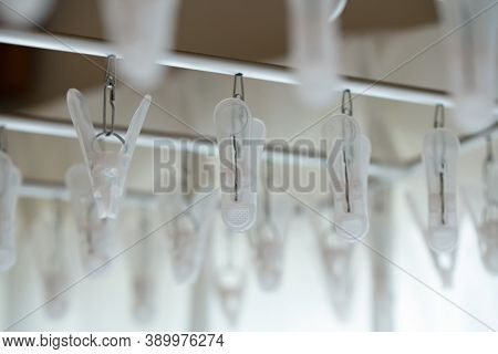 Laundry equipment in morning light. Laundry clip hanger or a drying rack, ready for drying laundered cloths. Shallow depth of field.