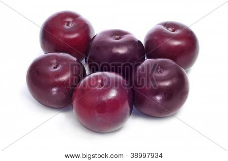 a pile of damson plums on a white background