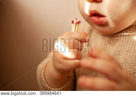 Hand Holding A Burning Match. Match With Fire And Flame On A Dark Background. The Concept Of Arson A
