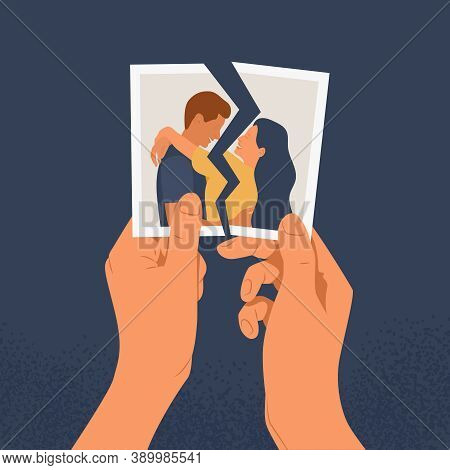 Hands Holding A Torn Photo Of A Couple In Love. The Concept Of Divorce, Separation And Broken Heart