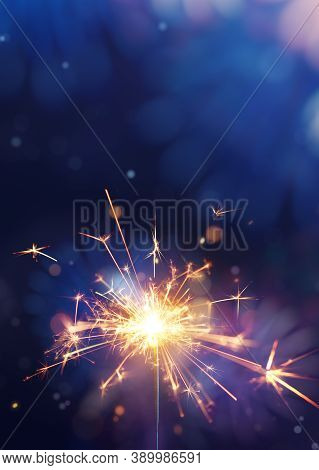 Glittering Burning Sparkler Against Fireworks Background With Copy Space