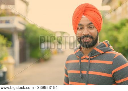 Young Handsome Indian Sikh Man Wearing Turban In The Streets Outdoors