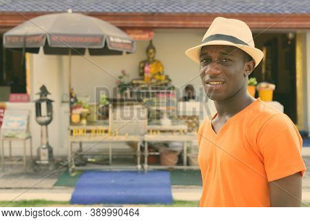 Young Black African Tourist Man Smiling Against View Of The Shrine Of Buddha Displayed With Offering