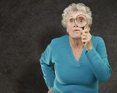 portrait of senior woman looking through a magnifying glass against a grunge wall poster