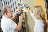 Assistant seller help choosing paint color and demonstrating matching samples to buyer at hardware store poster