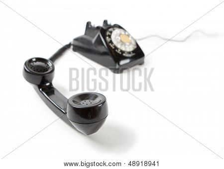 Old Late 60s - 70s style black telephone with rotary dial. Isolated on white. Hand set off the hook and unattended.