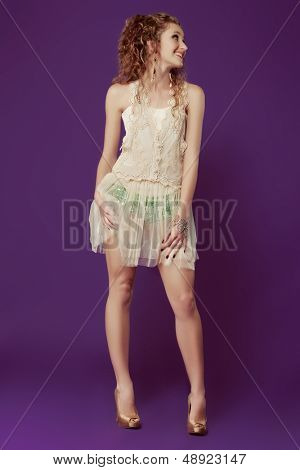 Beautiful young woman with long curly hair wearing lace dress over sequin shorts on purple studio background