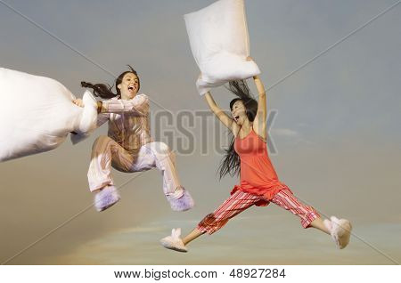 Two multiethnic young women having pillow fight midair outdoors