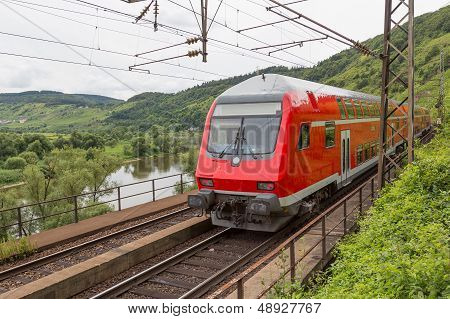 Train Driving Along River Moselle In Germany