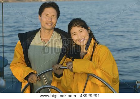 Portrait of smiling couple in yellow anoraks at steering wheel of sailboat against the sea