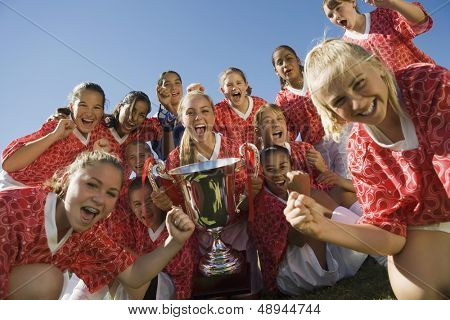 Portrait of excited girls' soccer team holding trophy against clear sky