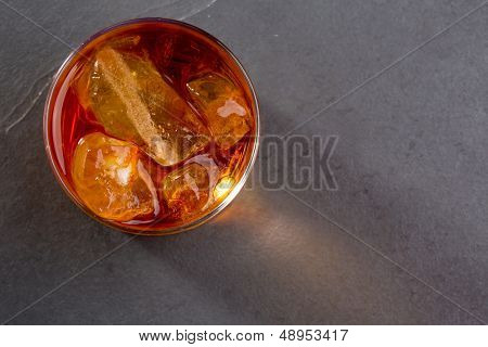 Whiskey whisky on the rocks on glass over gray black background