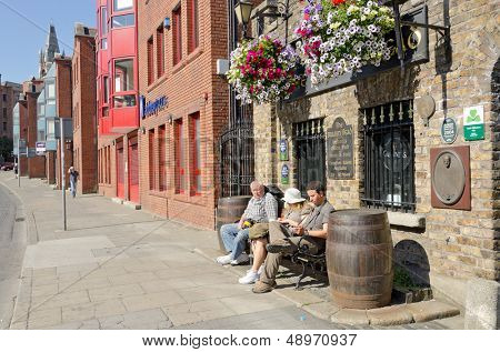 DUBLIN, IRELAND - JUNE 8: Family rests on bench in front of the oldest pub in Ireland,     The Brazen Head, Dublin, Ireland on June 8, 2013