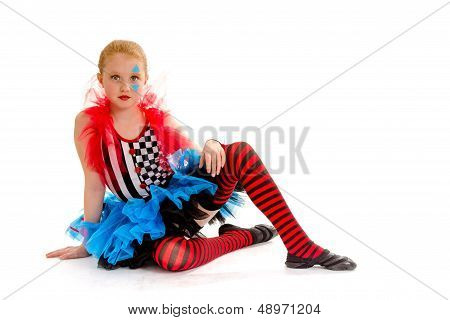 Seated Child Circus Jester In Colorful Costumer