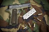 45 Firearm Pistol Clip And Hand Gun Ammunition on military camouflage background poster